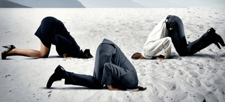 group of people in business attire on a beach with their heads in the sand