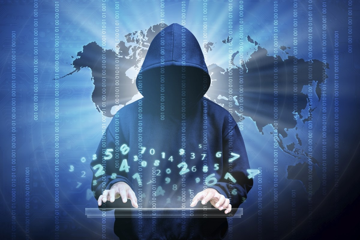 hooded hacker typing at computer with background of the world map